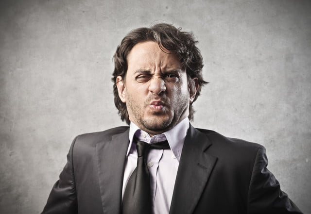 fart gasotransmitter  ortrait of businessman disgusted on a gray background