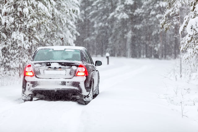 winter driving tips  land vehicle standing on a country road in wintry northern forest