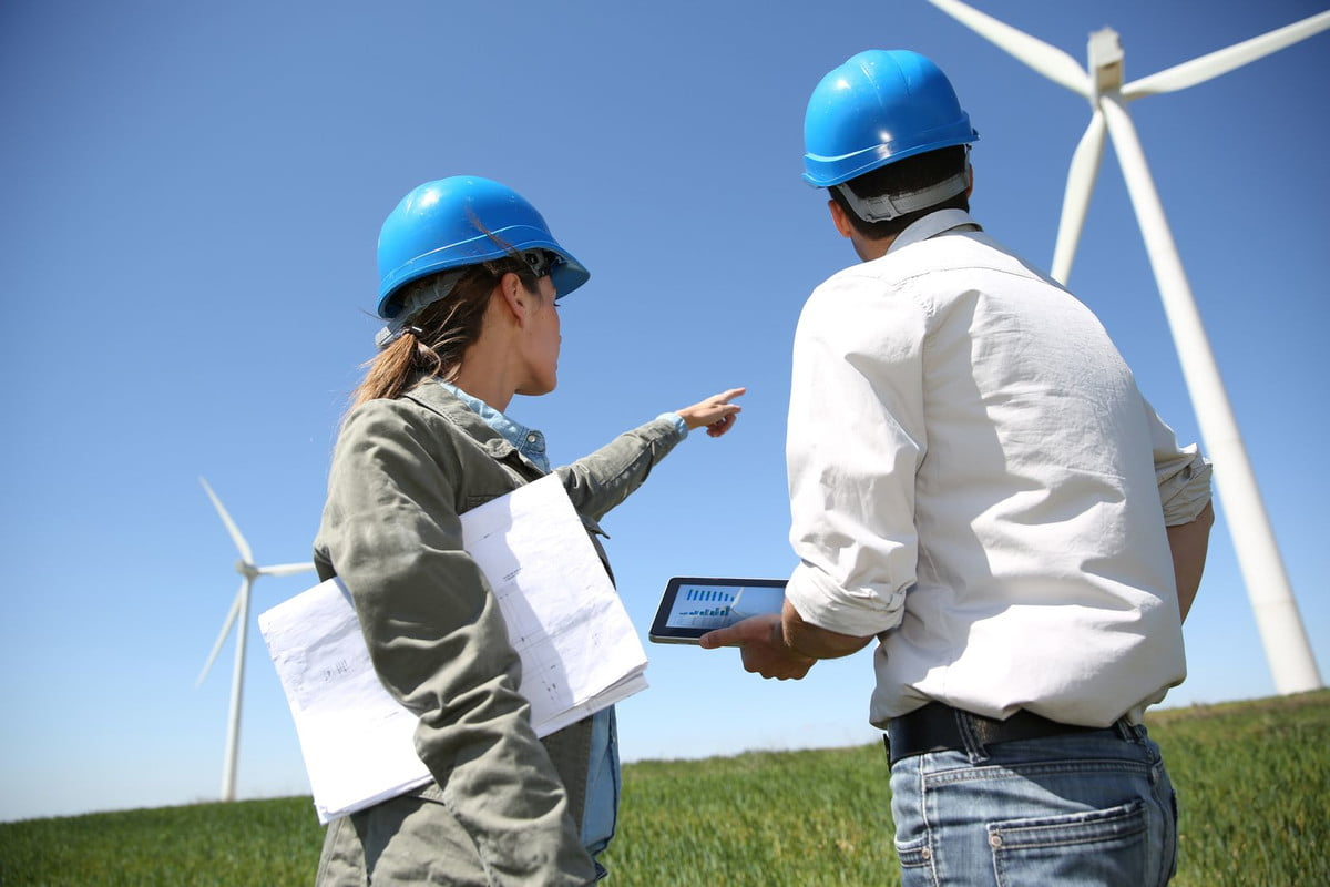 wind energy jobs  engineers looking at turbine site with tablet