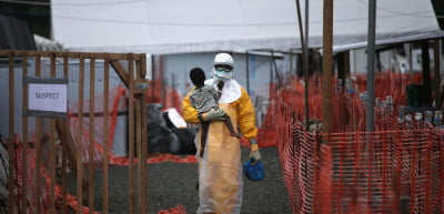 """John Moore, a Getty Images photographer, won the L'iris d'or grand prize of the 2015 Sony World Photography Awards with his series, """"Ebola Crisis Overwhelms Liberian Capital."""" In this image, """"An MSF health worker in protective clothing carries a sick girl at an Ebola treatment center."""""""