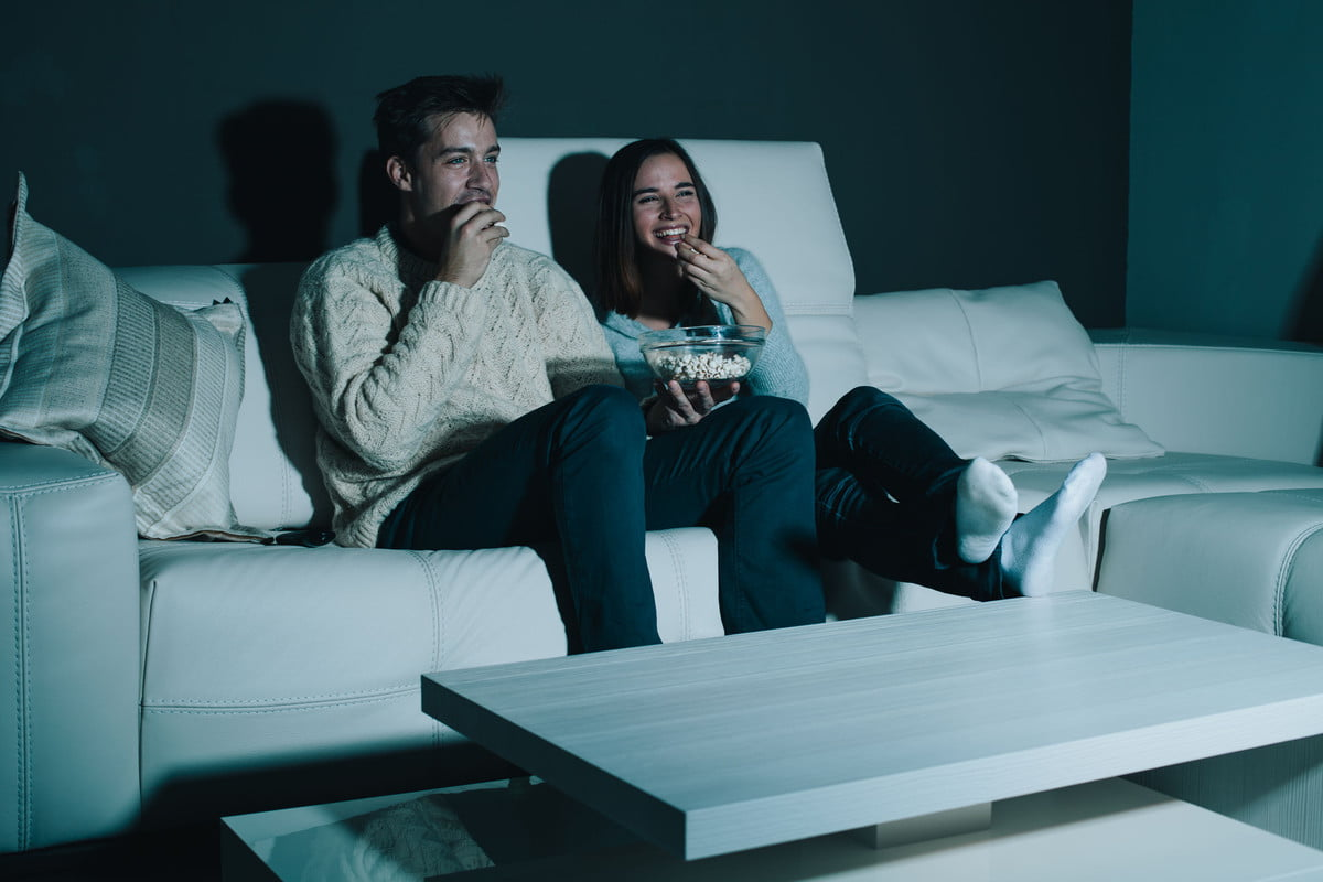 sling tv gets fandor festival starz channels couple enjoying watching a movie at home laughing on the couch