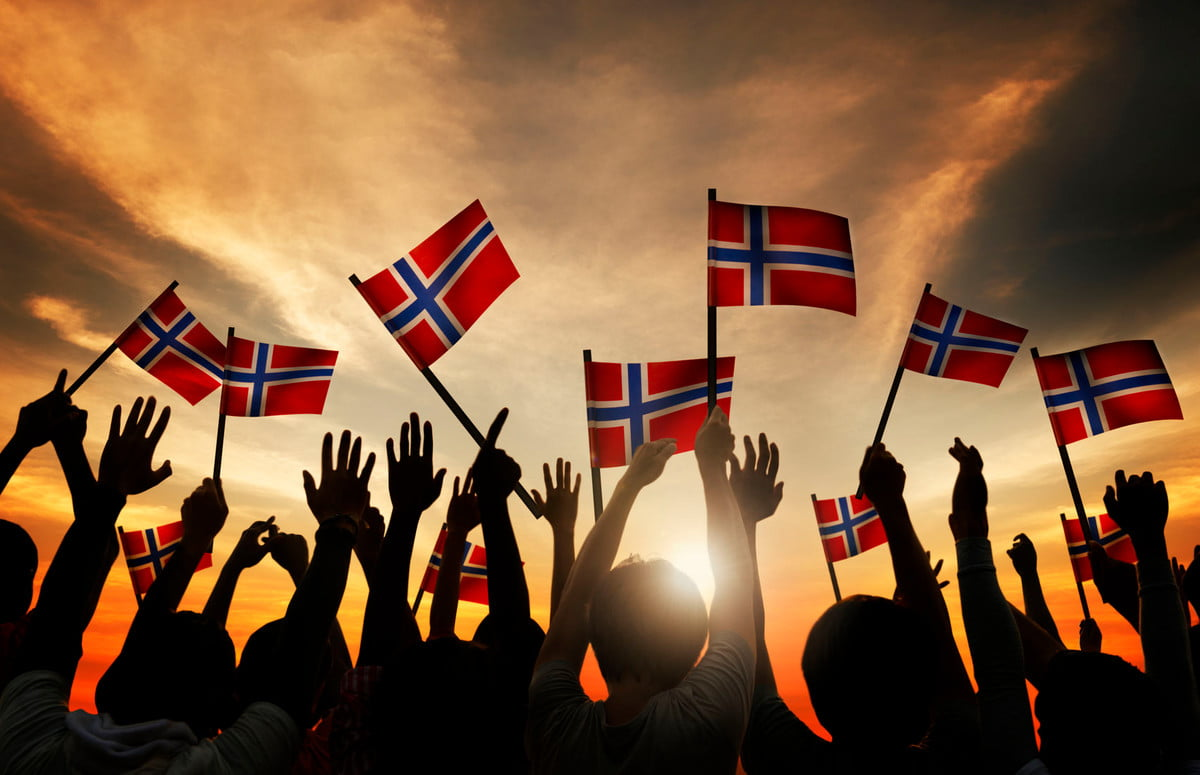 norway ev incentives extended  group of people waving norwegian flags in back lit