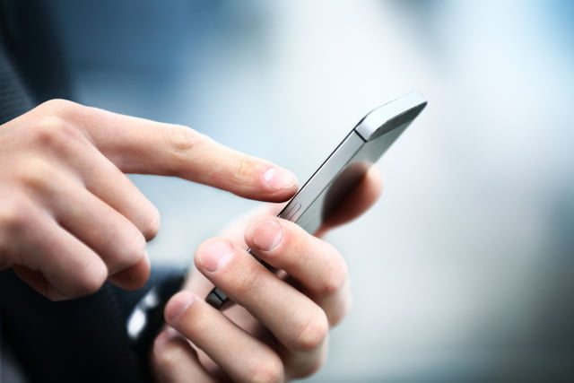 court text messages coercive  close up of a man using mobile smart phone