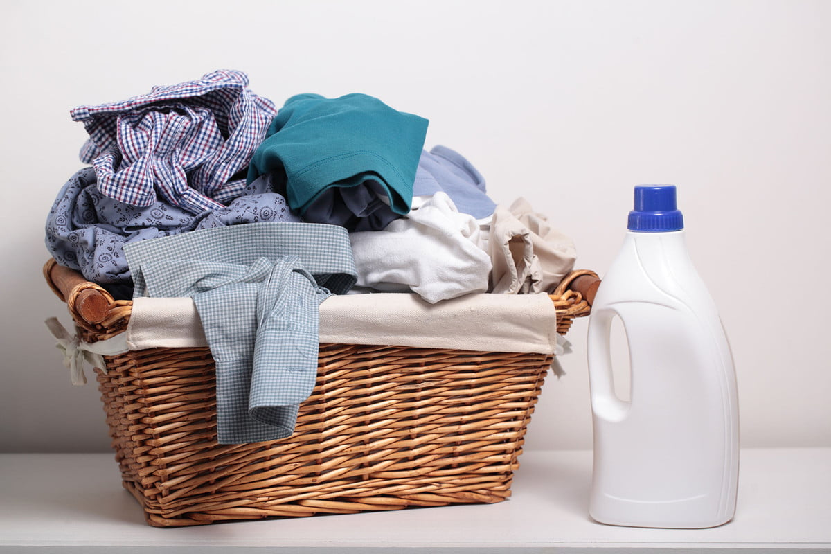 how much laundry detergent should you use  dirty clothes in the basket and a bottle of