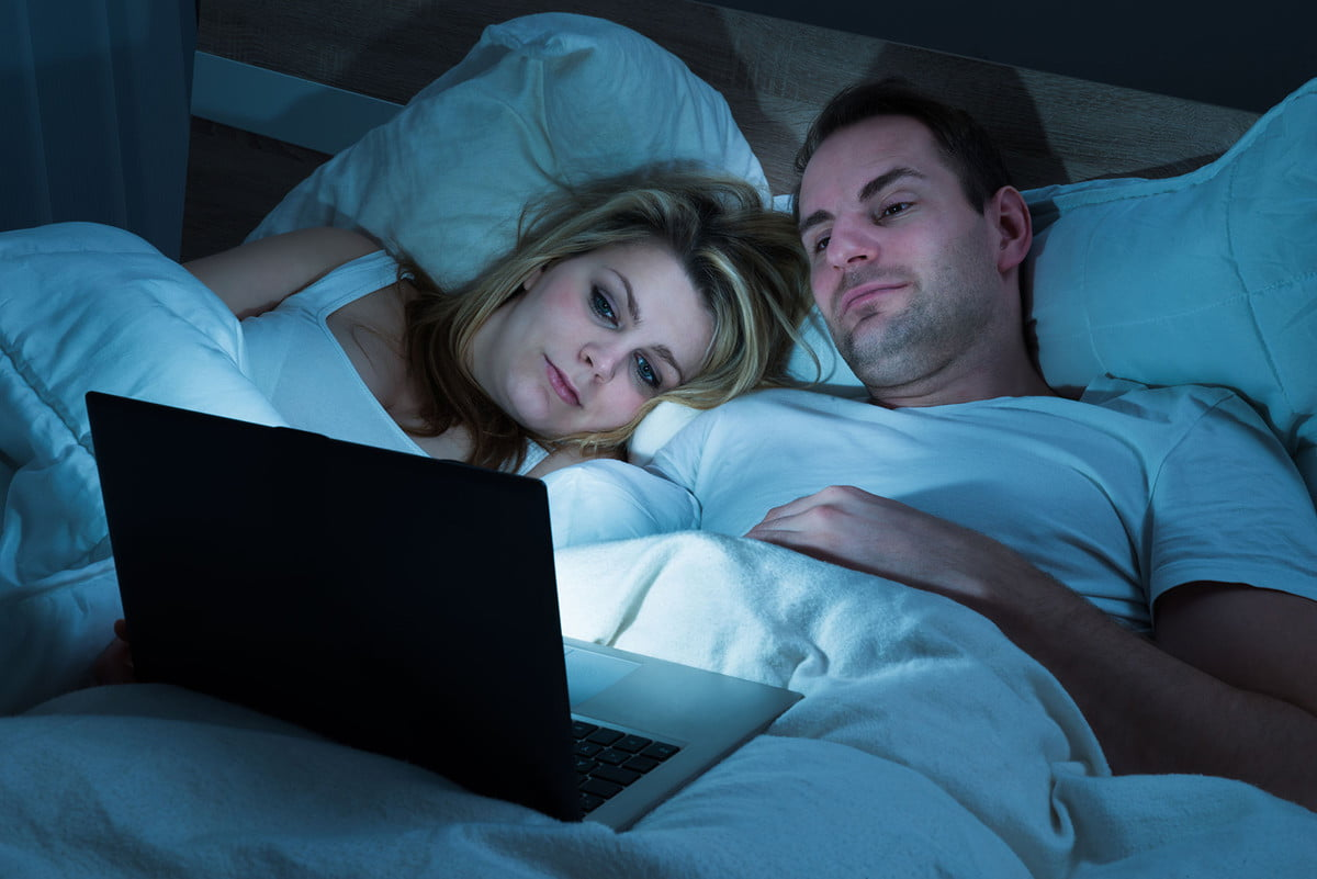 where to watch free movies online  couple lying in bed with blanket looking at laptop