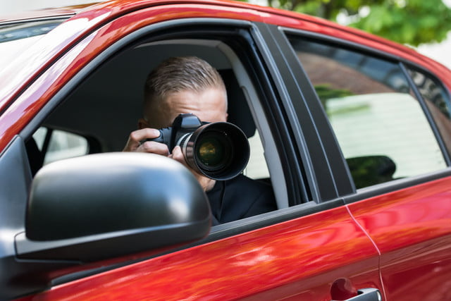 personal profiles databases records private investigators source  close up of a male driver photographing with slr camera fro