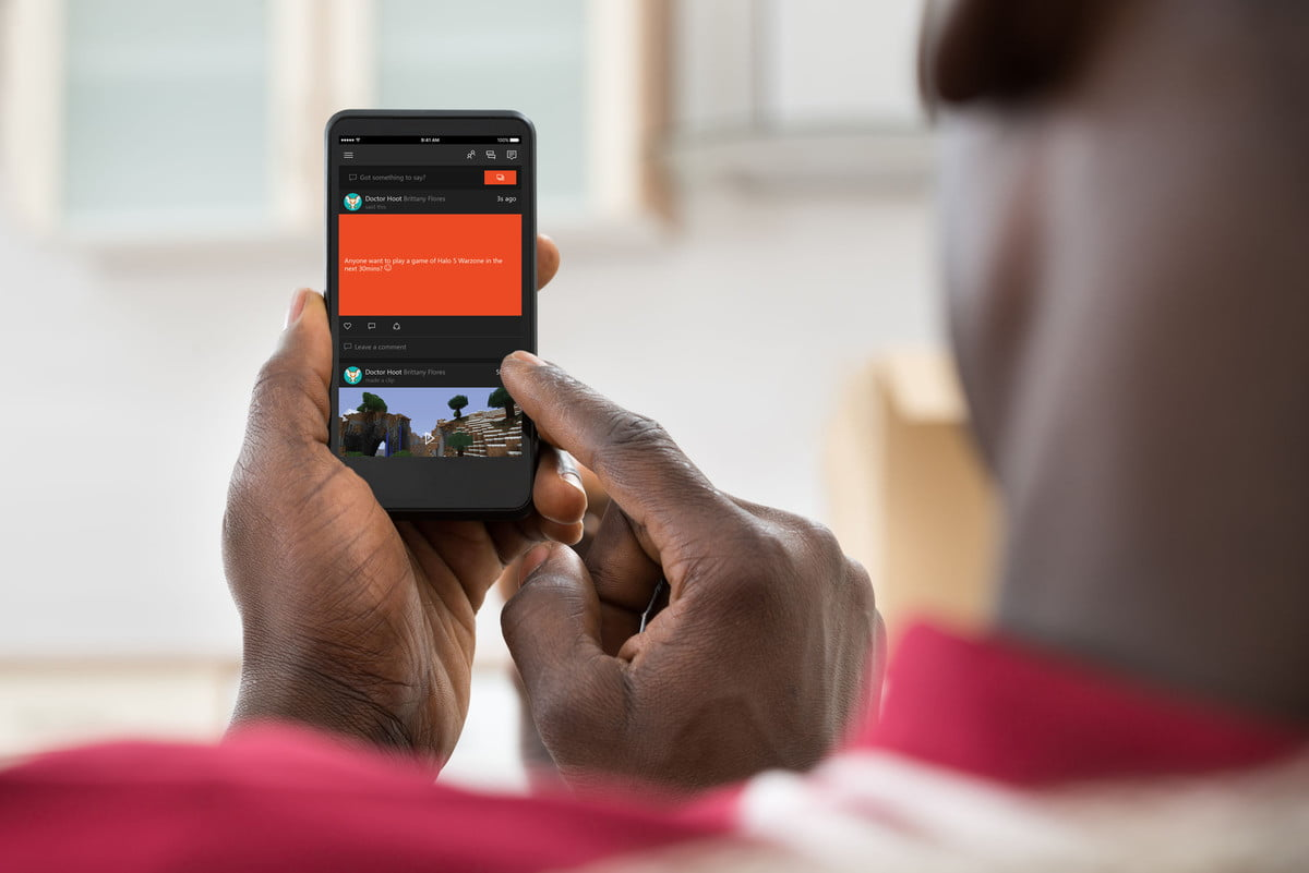 connect smartphone xbox one  close up photo of african man holding cellphone
