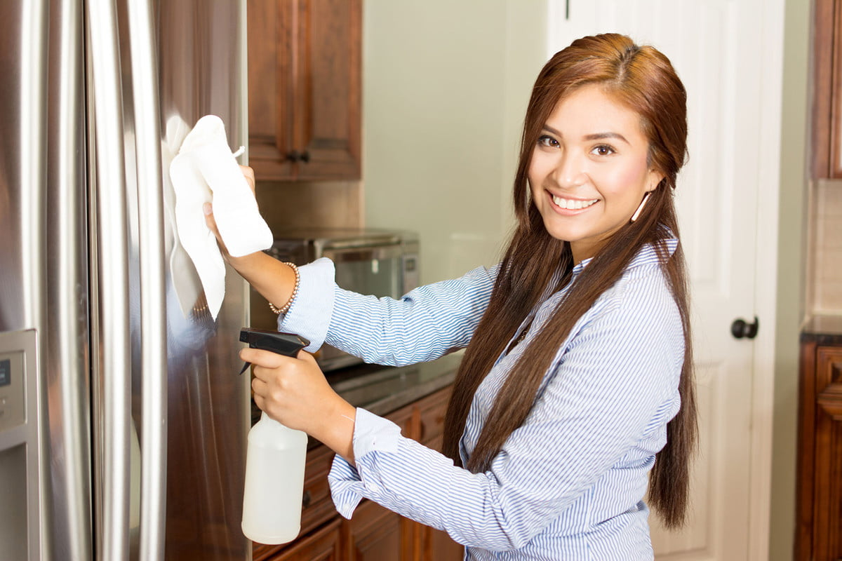 how to clean stainless steel appliances  woman cleaning her kitchen with a spray bottle