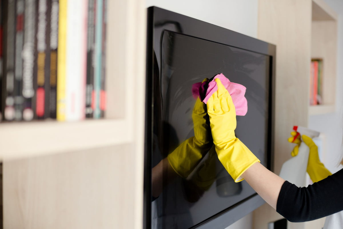 how to clean your lcd or plasma tv  woman in yellow rubber gloves cleaning with pink cloth