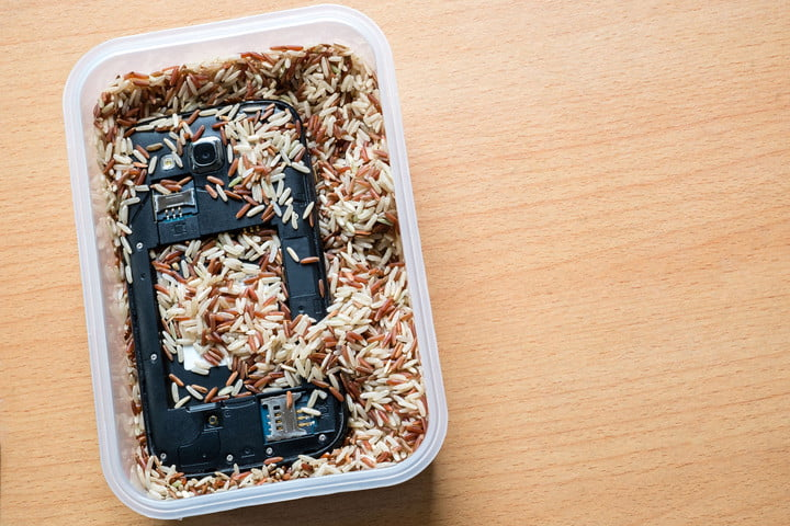 62051475 - mobile phone in milled brown rice. save wet phone.