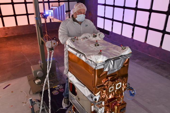 A Ball Aerospace engineer adjusting the thermal insulation on a GPIM spacecraft bus