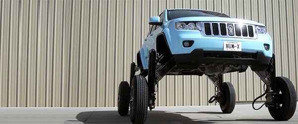 Rise up! Watch this modded-out Jeep lift itself 9 feet and straddle smaller cars