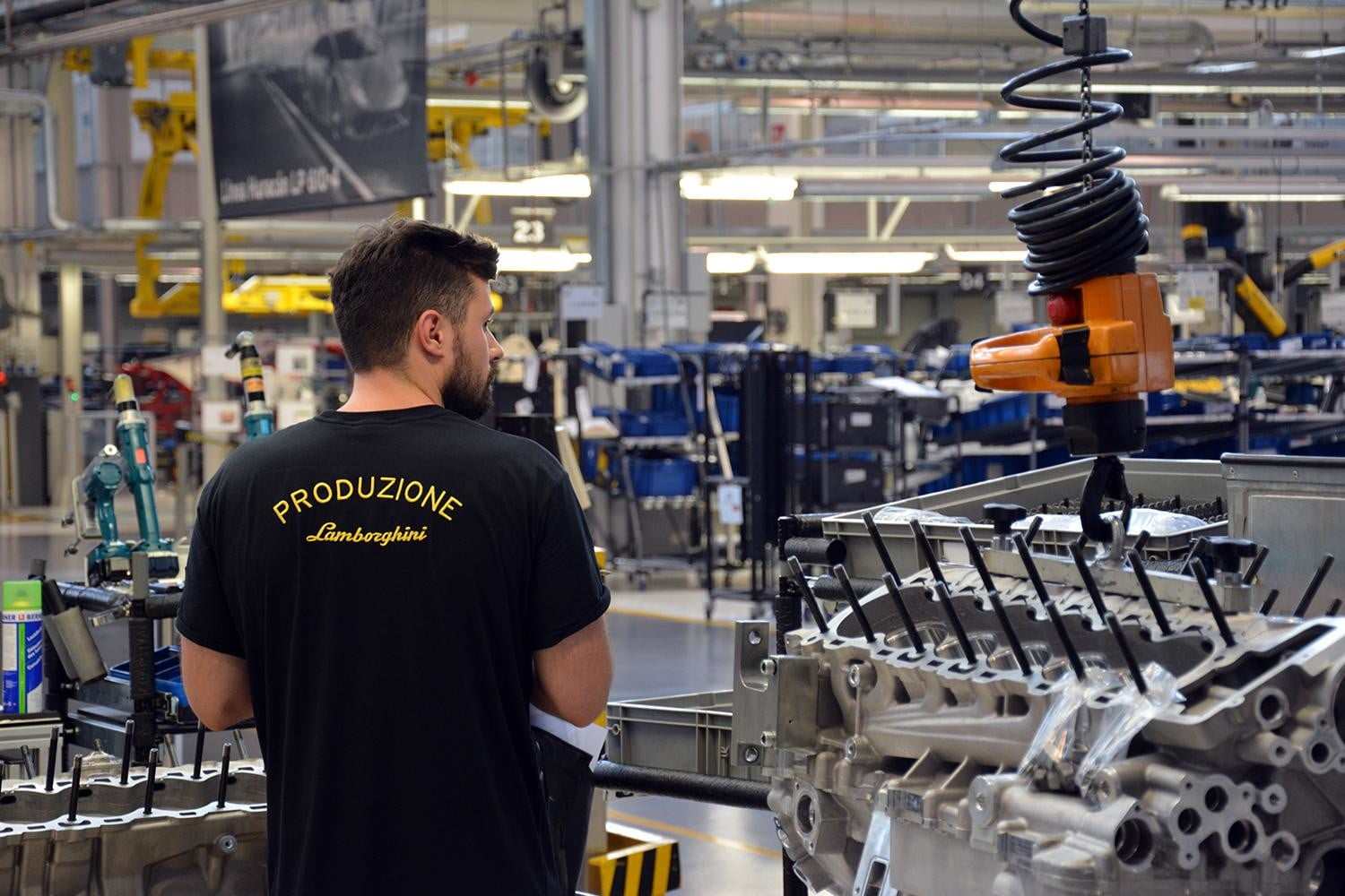 """Employees wear a black Lamborghini uniform that clearly indicates whether they're assembly line workers, part of the factory's logistics team, assigned to the prototype-building division and so forth. """"Produzione"""" (Italian for """"production"""") means the man pictured here is an assembly line worker."""