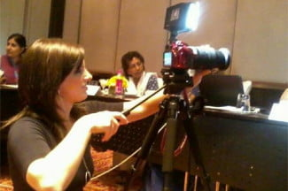 Lindsey Mastis operates her own camera as she reports from the field.