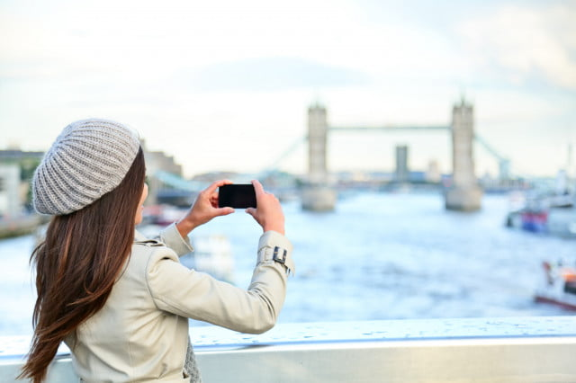 London woman tourist taking photo on Tower Bridge