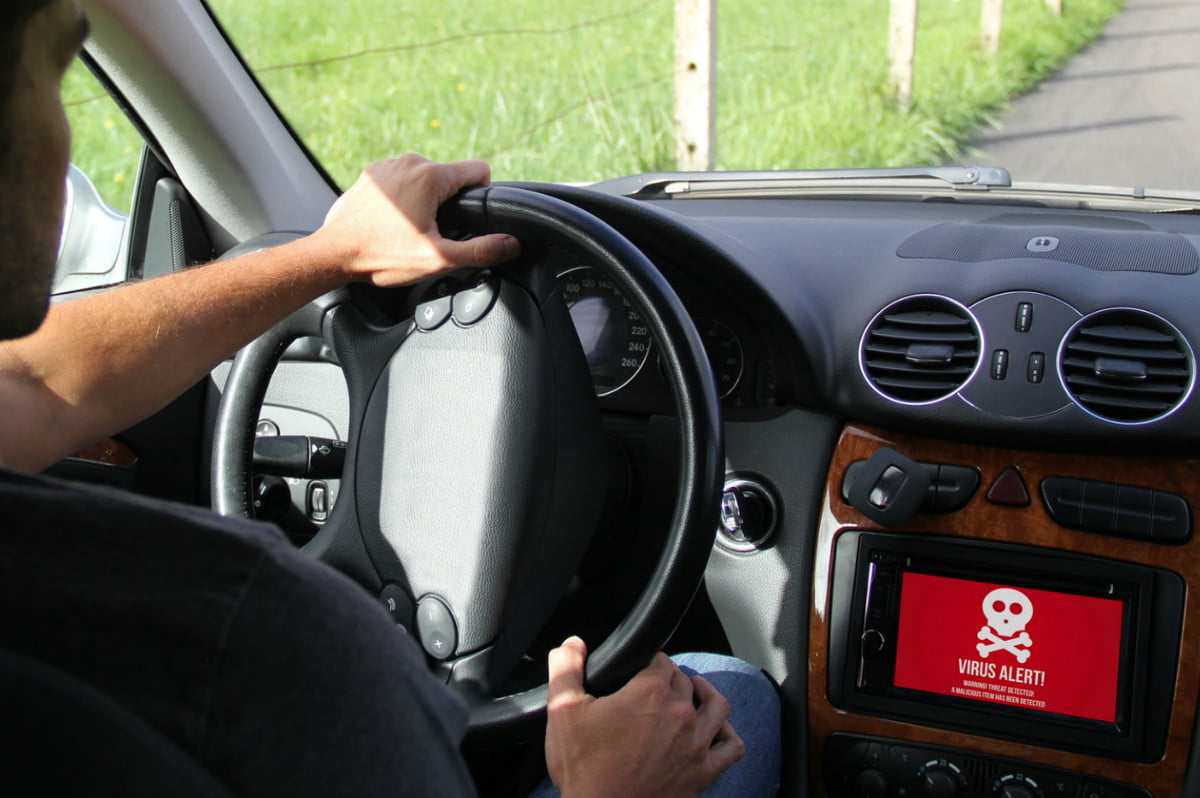 connected car app security man driving a hacked showing on board screen computer virus alert