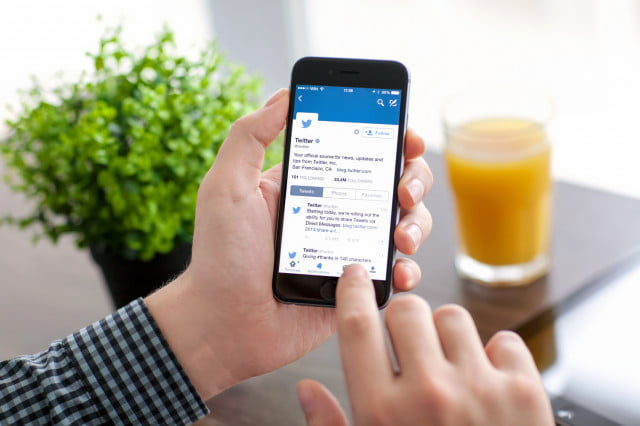 twitter algorithmic timeline opt out man holding iphone  with on the screen