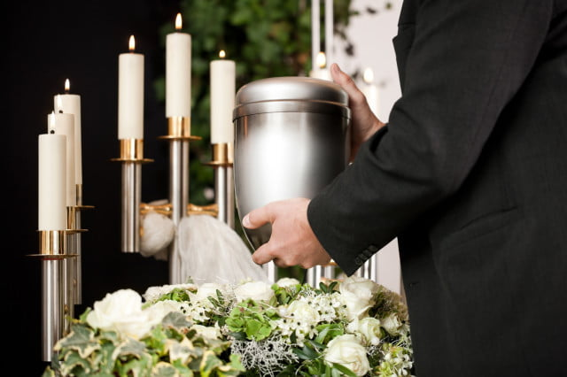 dna home storage man placing urn by candles at funeral