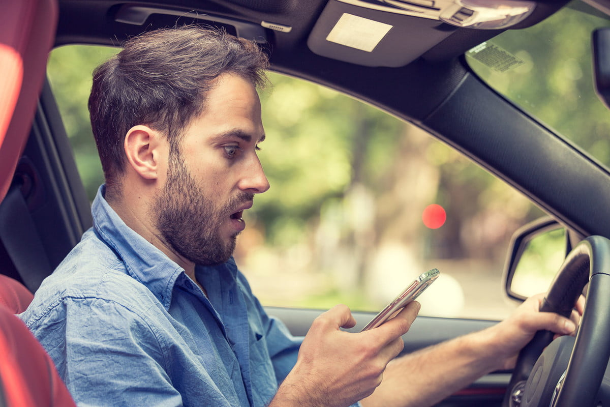 sat nav brain activitys man sitting in car with mobile phone hand texting while driving