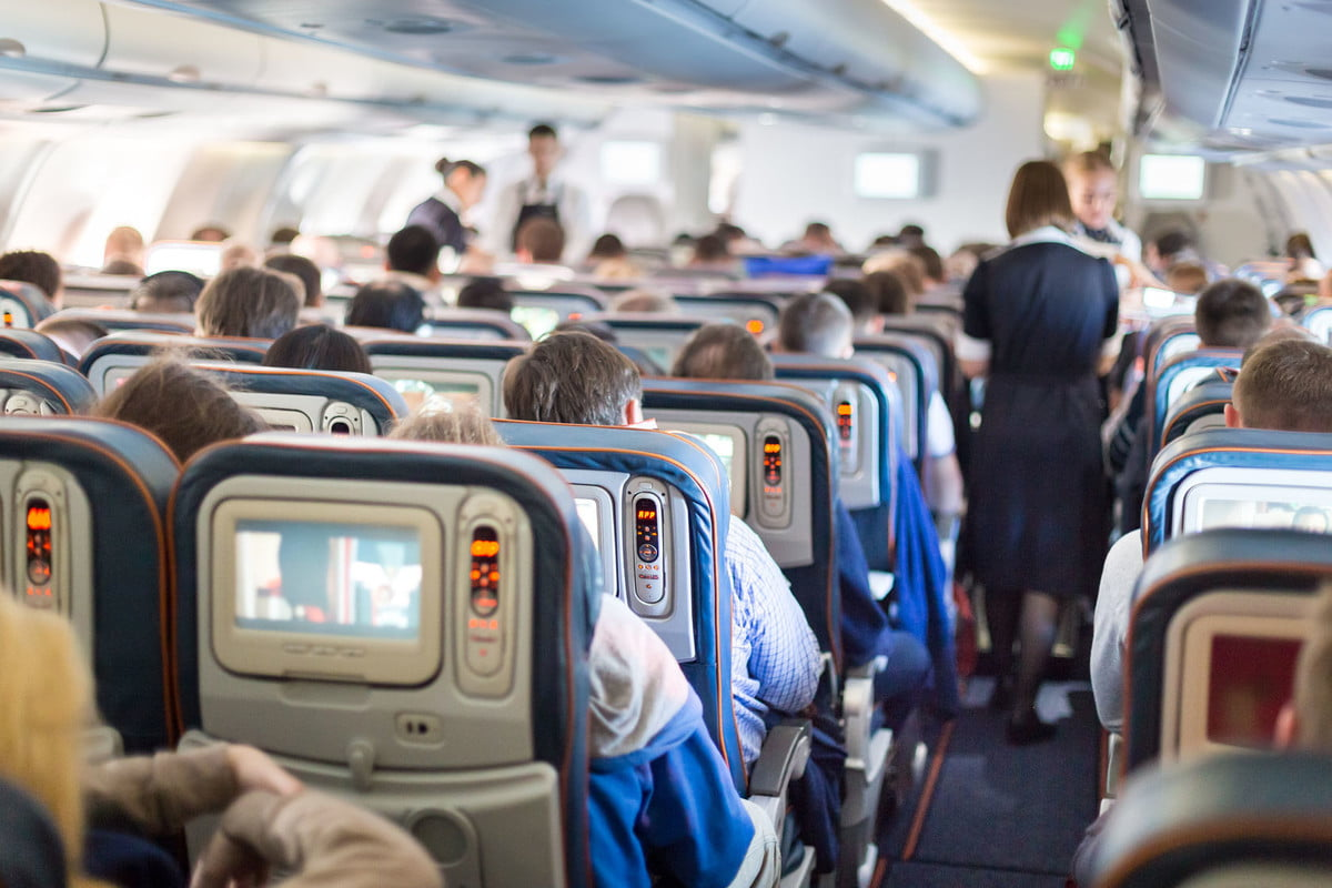 in flight wi fi many compromises nterior of large passengers airplane with people on seats and stewardess uniform walking the