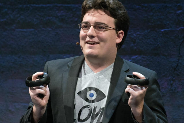 Oculus founder Palmer Luckey holds up Oculus Touch prototype controllers.