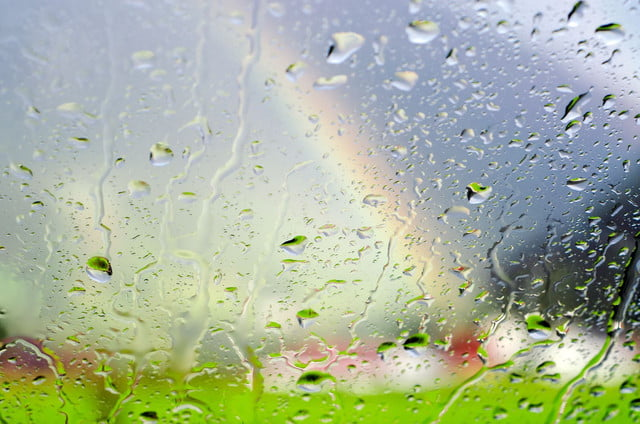 high humidity weakens radio signals lte raindrops on glass panel with scenery and rainbow in background