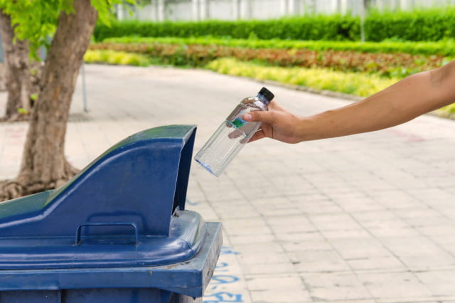 recyclable bioplastic recycling throwing into trash can bottle bin garbage