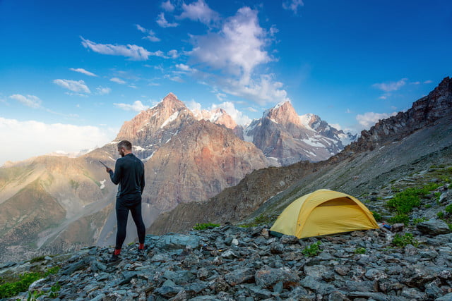 satellite phone buying guide silhouette of man in wild mountain landscape walk along yellow camping tent holding