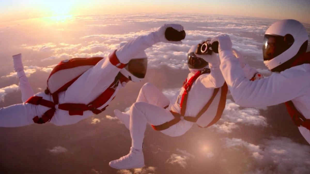 epic sony ad shows skydivers changing lens of alpha a r in midair change