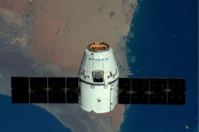 look what photobombed iss astronauts photo of earth spacex dragon capsule