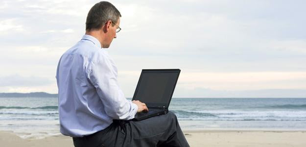 using laptop on beach vacation