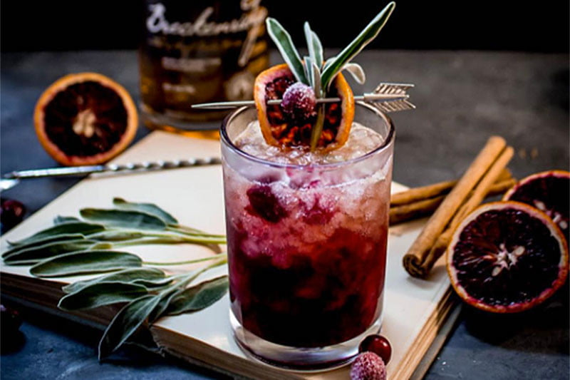 Cocktail with blood orange and sage garnishes