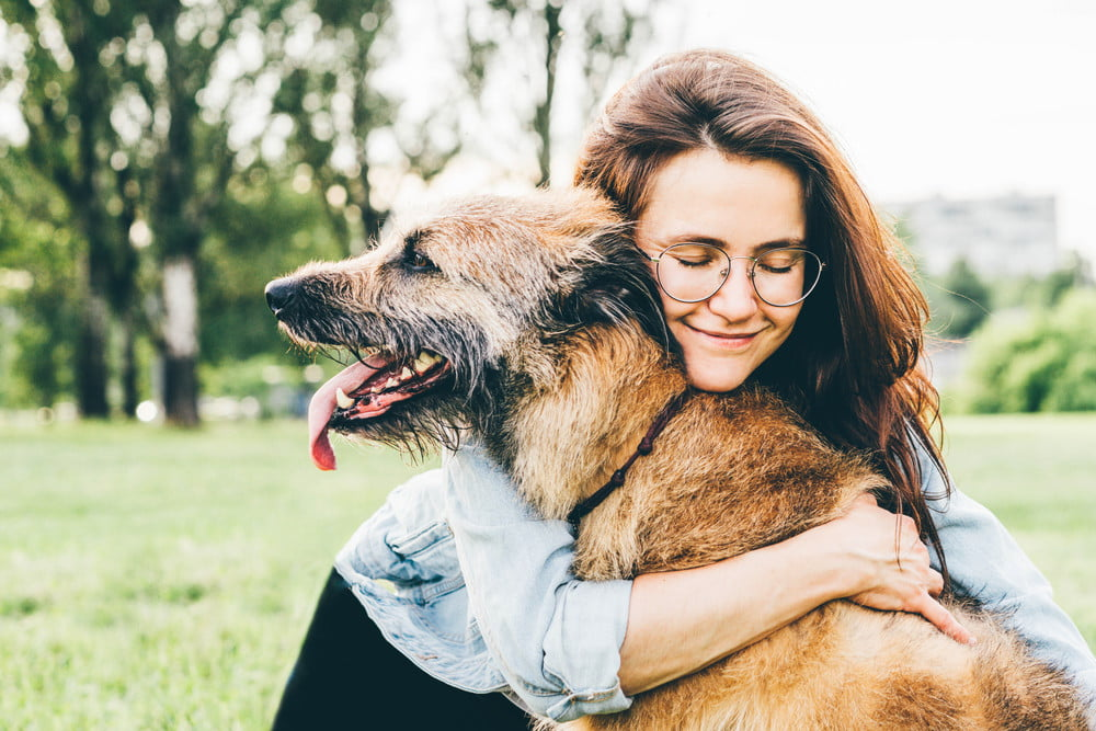 A woman in glasses holding an old brown dog.