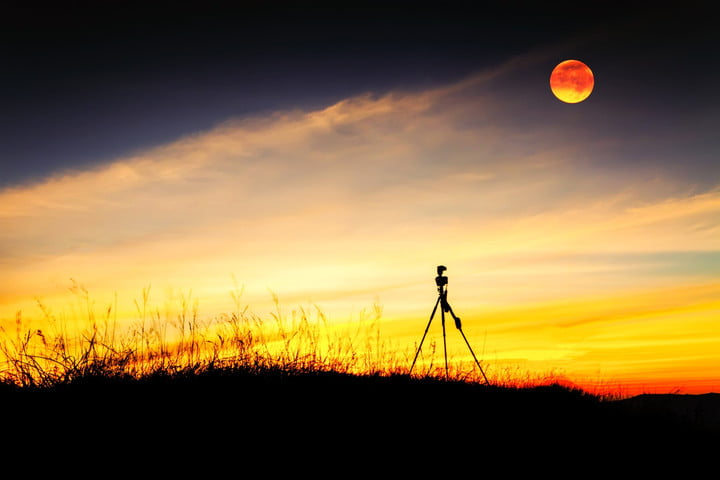 Tripod stand on mountain with moon at after sunset.