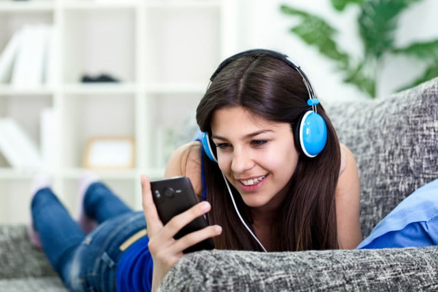 vevo mobile relaunch youtube woman listening to music on smartphone with earbuds