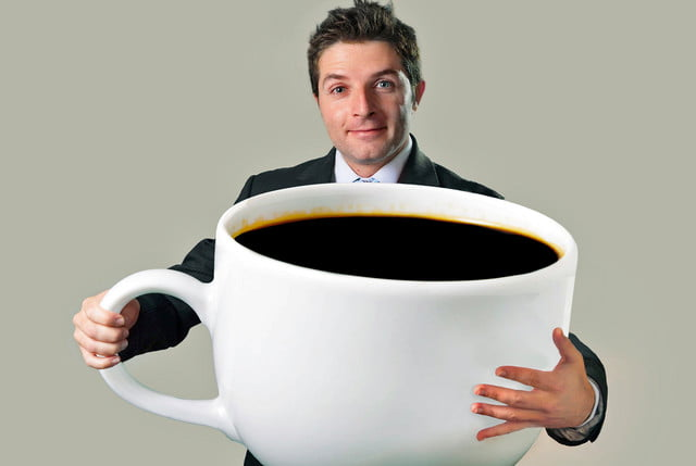 coffee not carcinogenic superheated beverages are young happy business man holding a funny huge and oversized cup of black  x