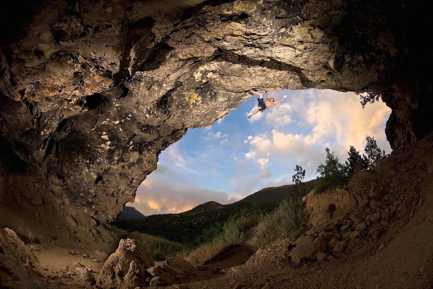 """Timy Fairfield hanging from the lip of the Crystal Cave on """"Super-Dope"""" (5.13b) near Jemez Springs, New Mexico."""
