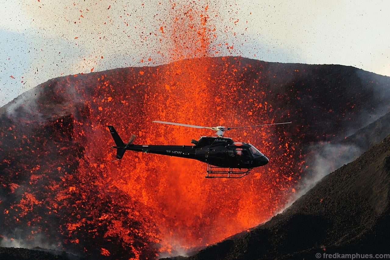 A helicopter flies close to one of the craters of the 2010 Fimmvörðuháls eruption in Iceland.